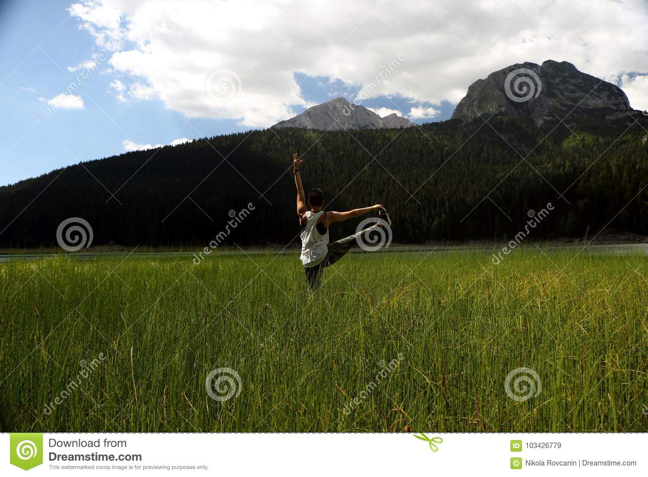Woman practicing yoga in the grass