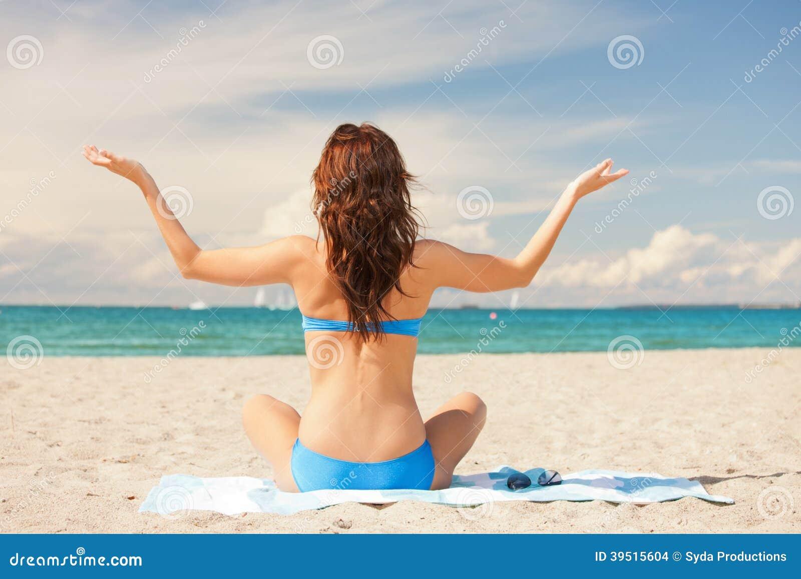 Woman practicing yoga lotus pose on the beach