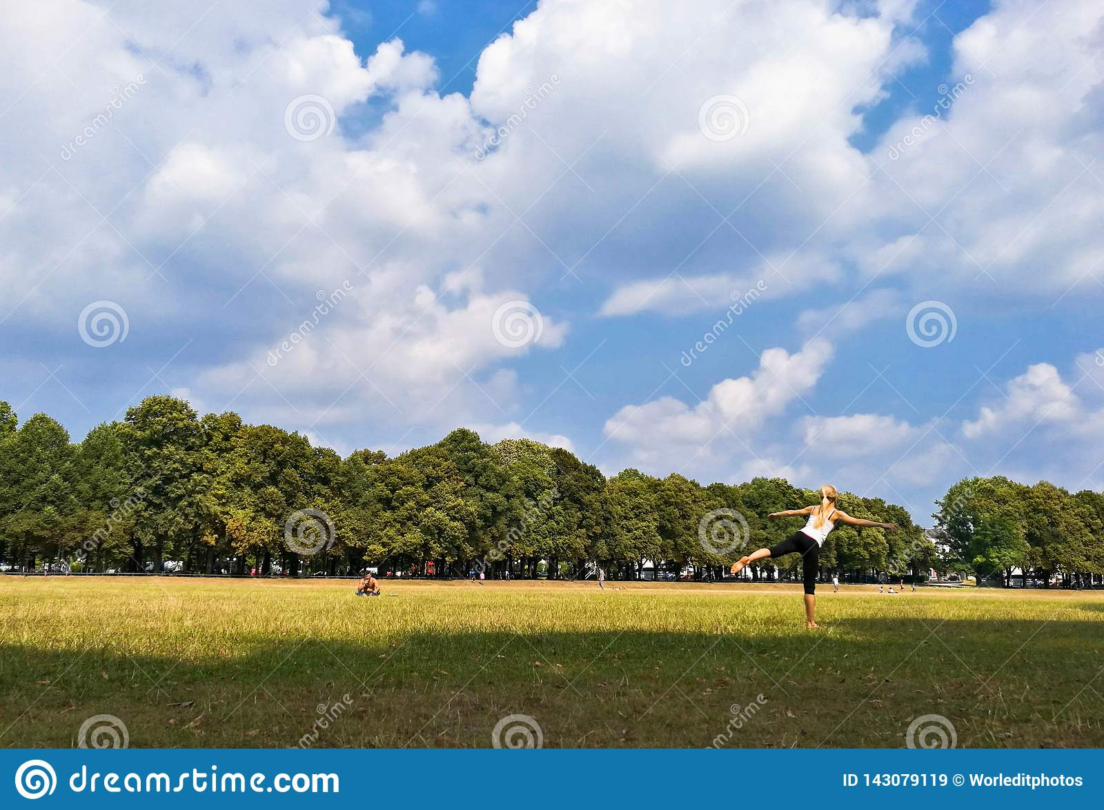woman practicing yoga outdoor in the park on a sunny day