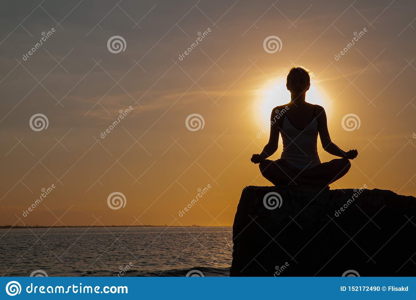 Woman is practicing yoga sitting on stone in Lotus pose at sunset. Silhouette of woman meditating on the beach