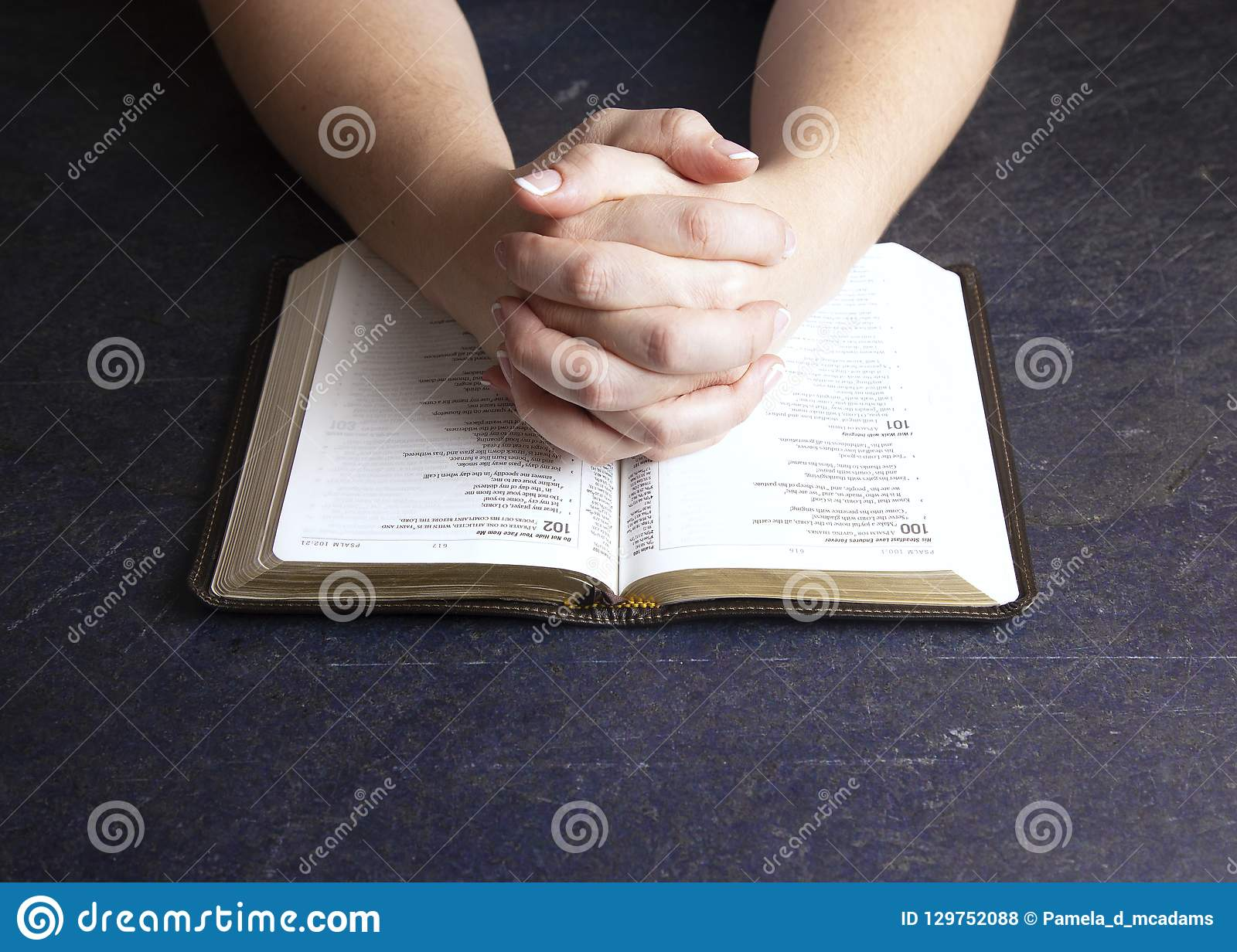 Woman Praying With Her Hands Clasped On A Bible Stock Photo