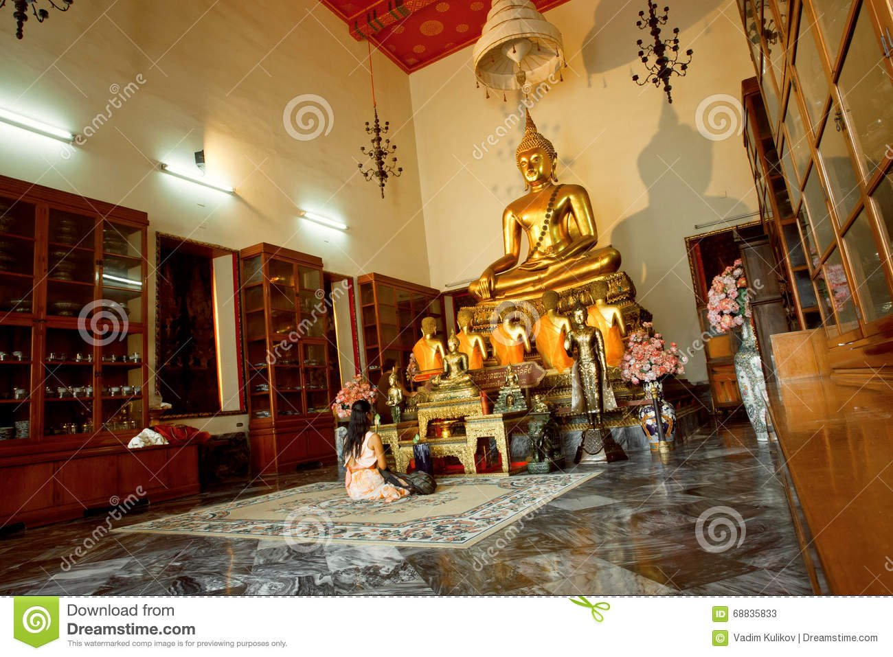Woman Praying Past Buddha Statue Inside Small Temple Room Of