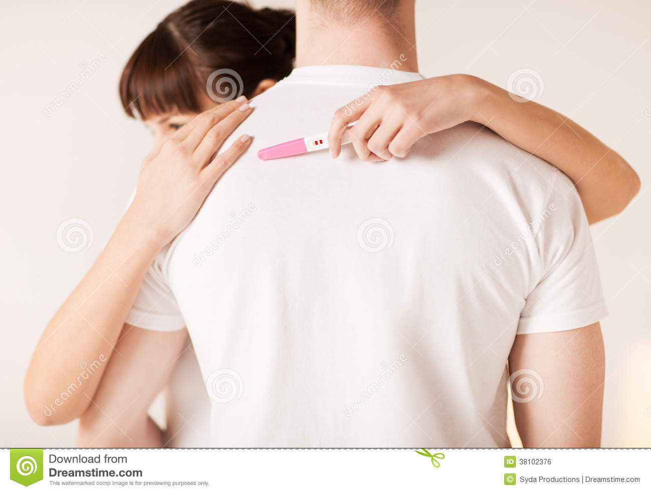 Woman with pregnancy test hugging man
