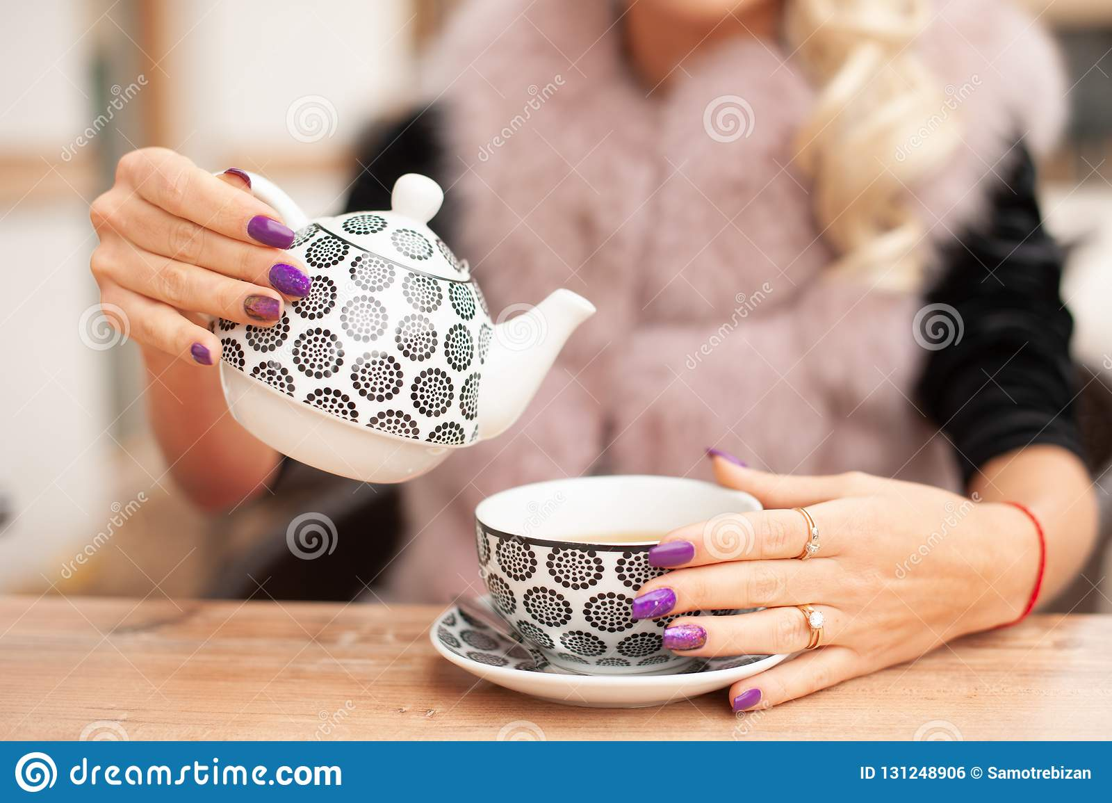 Woman prepare tea on bar terace hold teapot in her hands in ear