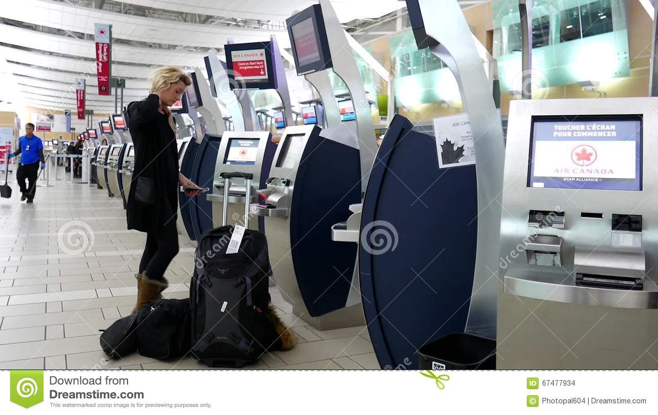 Woman Printing Out Boarding Card At Air Canada Machine Stock Footage