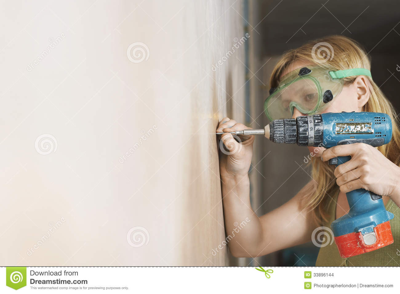 Woman In Protective Goggles Drilling Wall