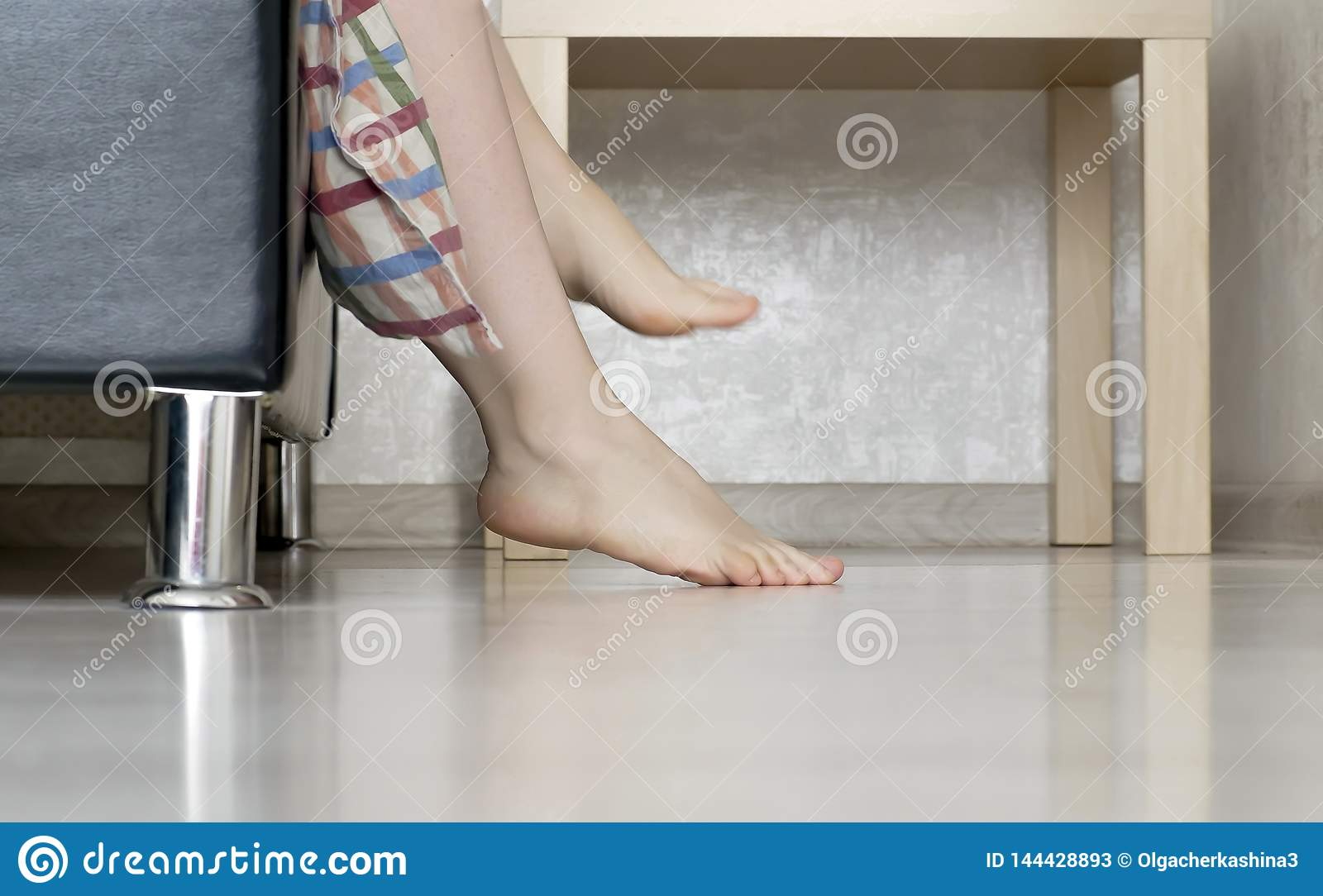 Woman pulls her legs out of bed