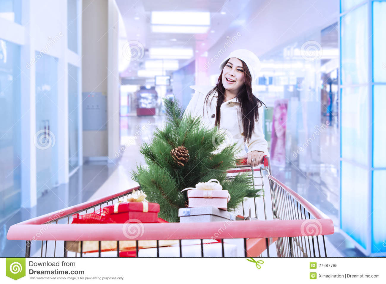 Woman push shopping trolley with christmas tree