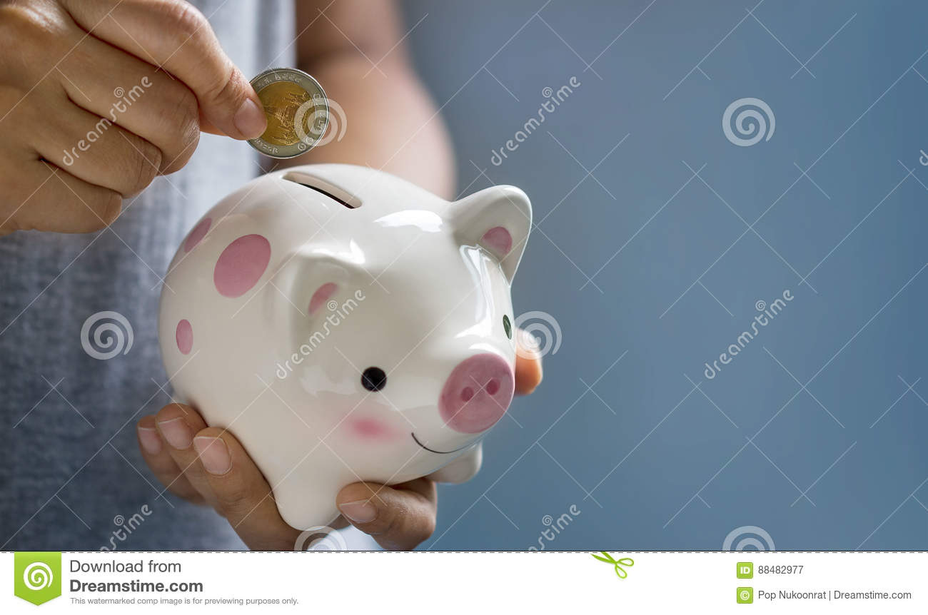 Woman putting coin into piggy bank for saving
