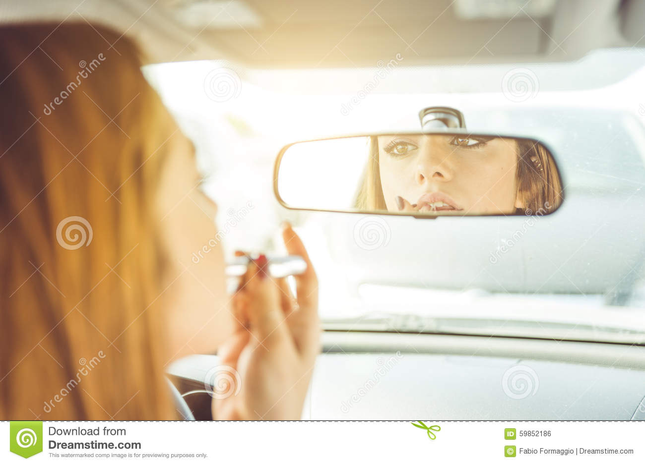 Woman putting lipstick in the car.