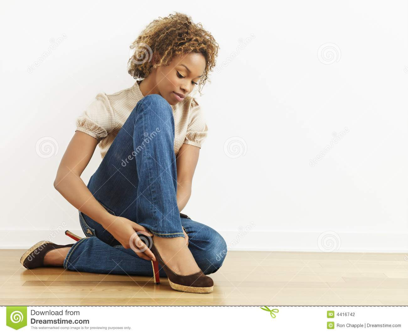 Woman Putting On Shoes Stock Photography - Image: 4416742