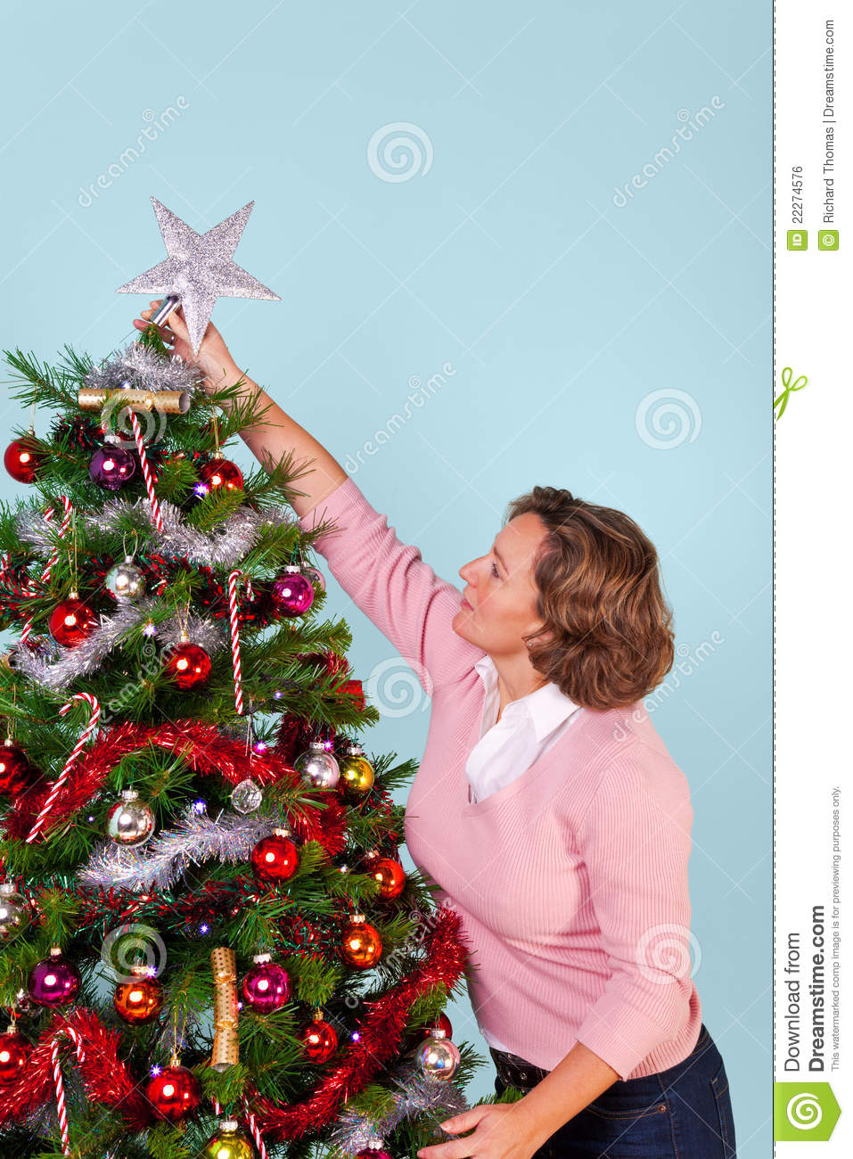 woman putting star on top of christmas tree stock photo image of