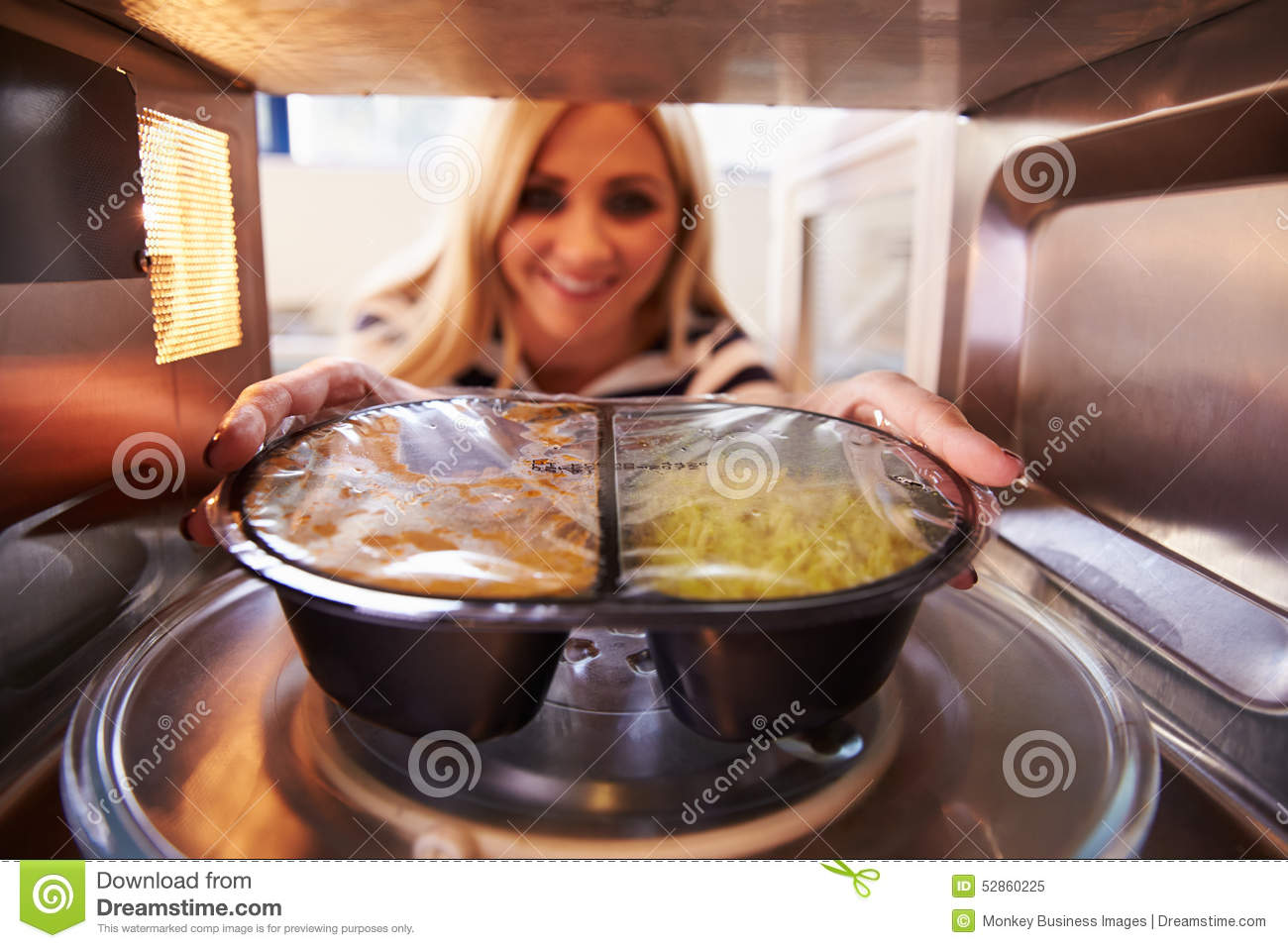 Woman Putting TV Dinner Into Microwave Oven To Cook