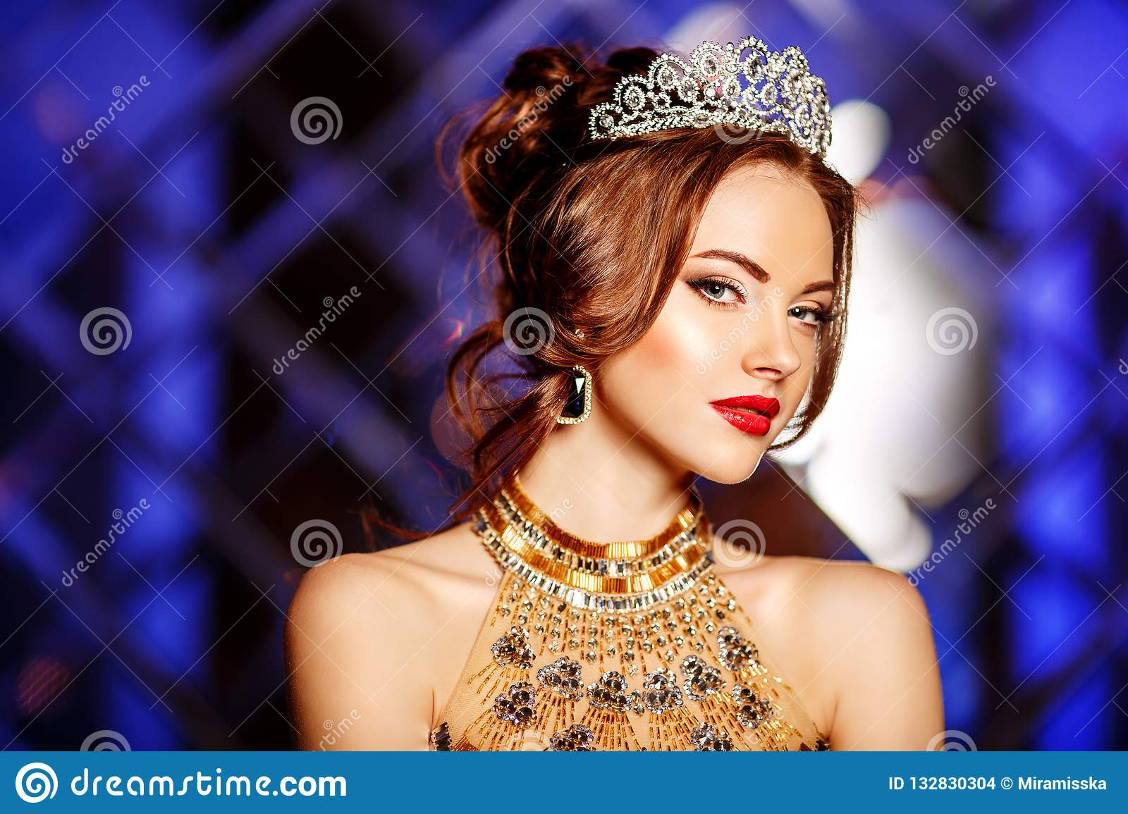 Woman queen princess in crown and lux dress, lights party background Luxury girl Long shiny healthy volume hair Waves Curls