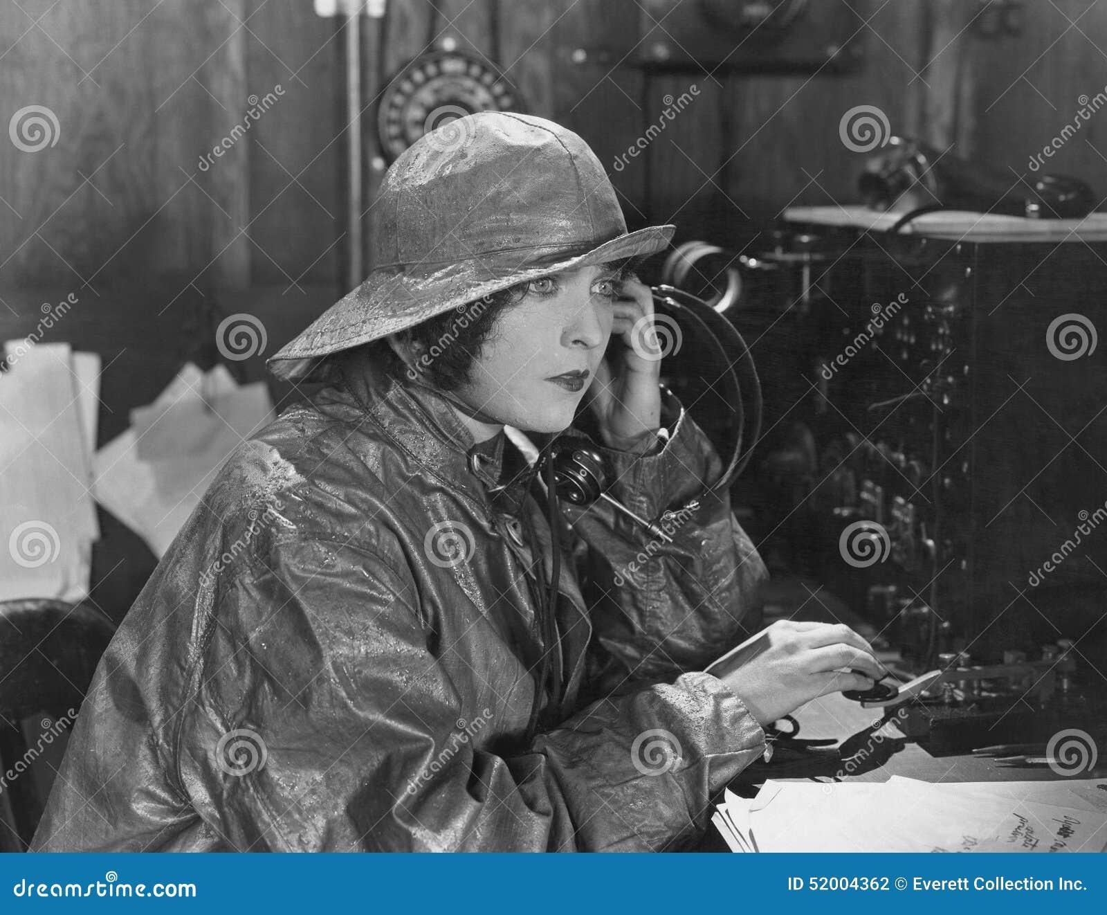 woman in raincoat sending message in morse code stock