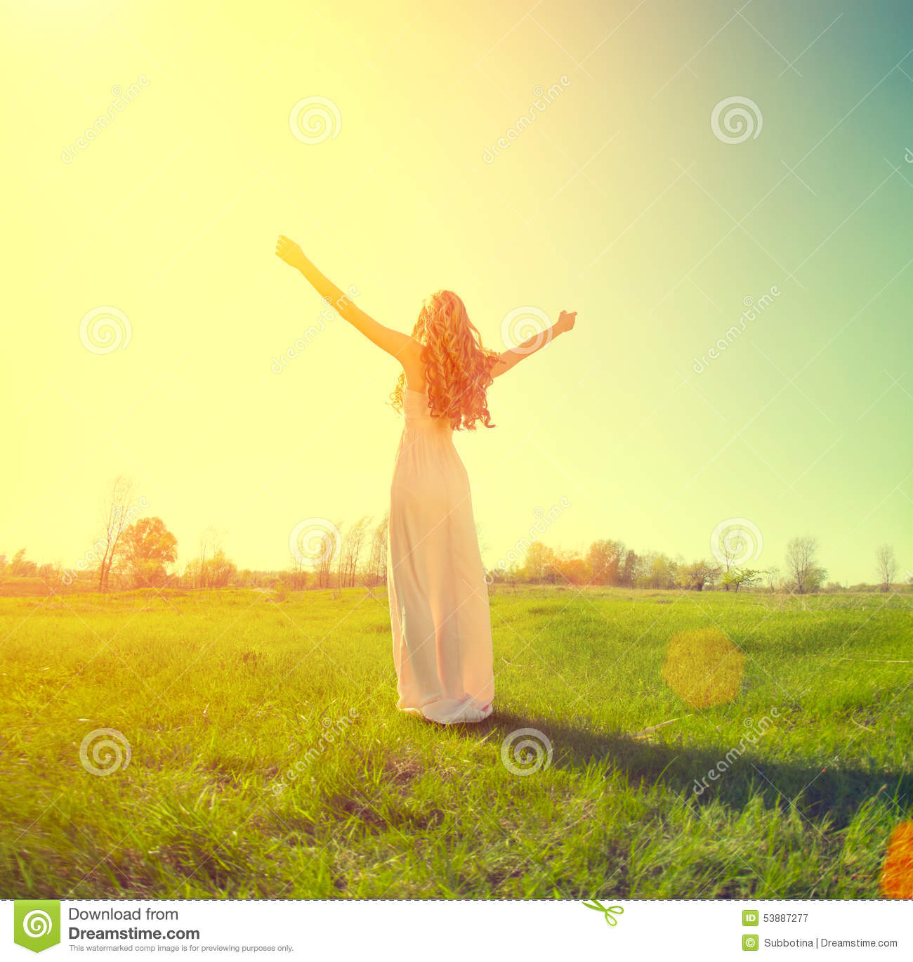 Woman raising hands in sunlight rays