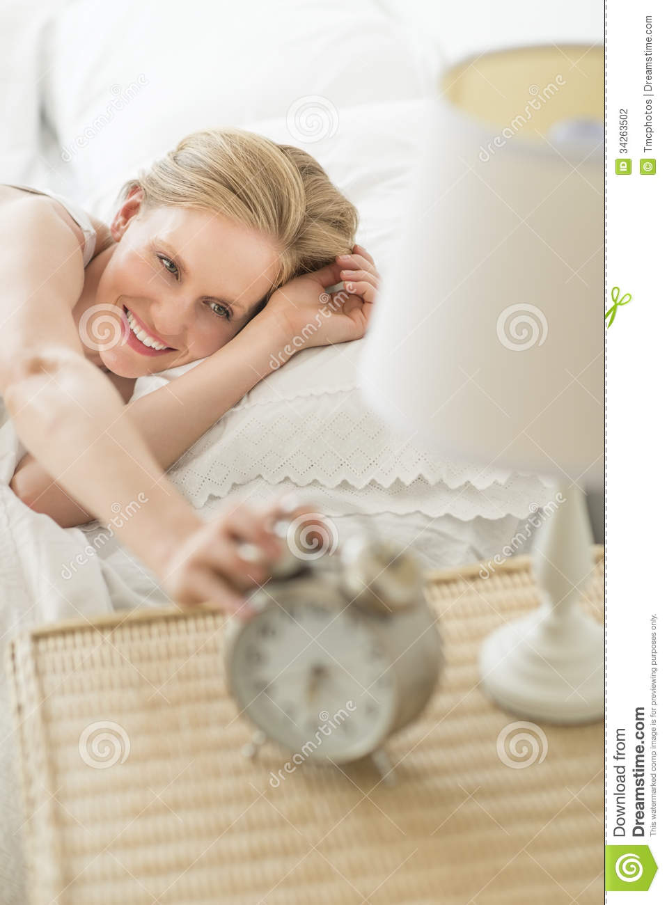 Woman Reaching For Alarm Clock While Lying On Bed
