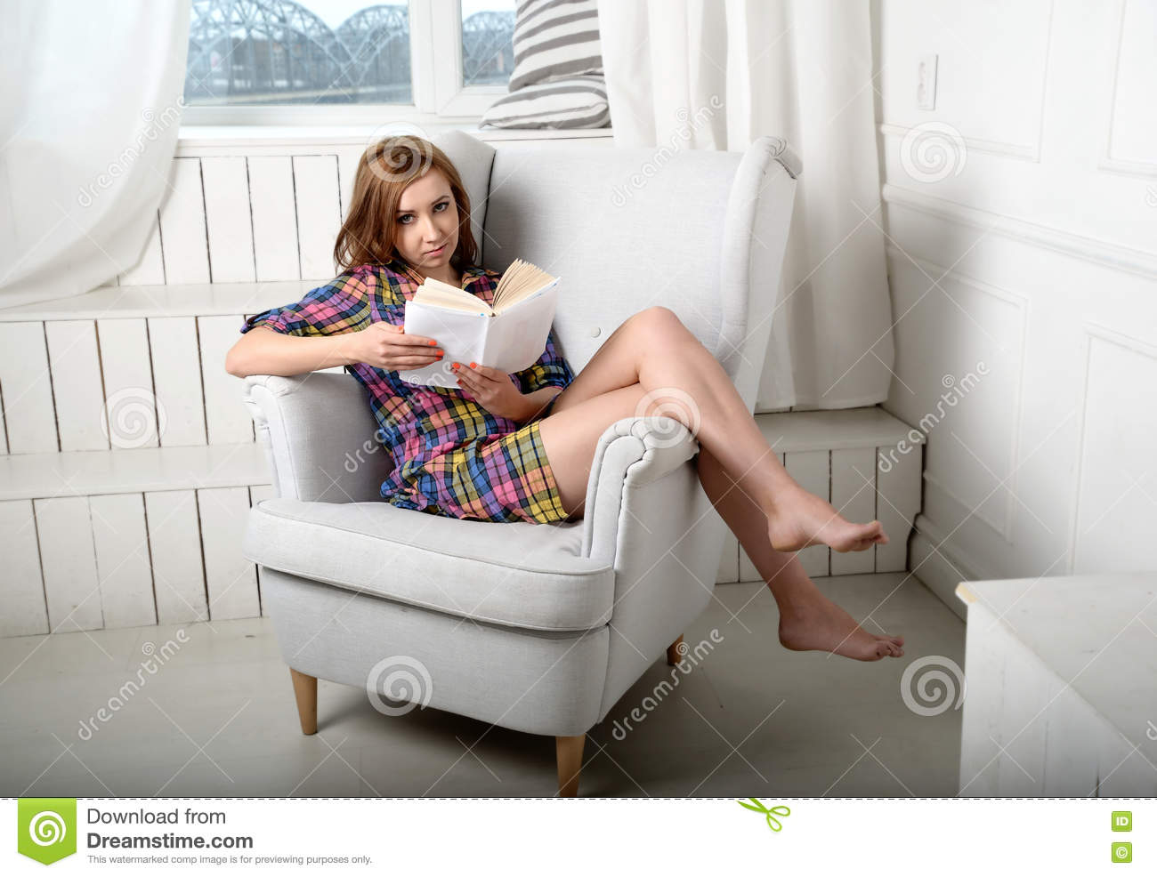 7f3949ee6445 Photo of a woman reading a book on the couch. Portrait photography.