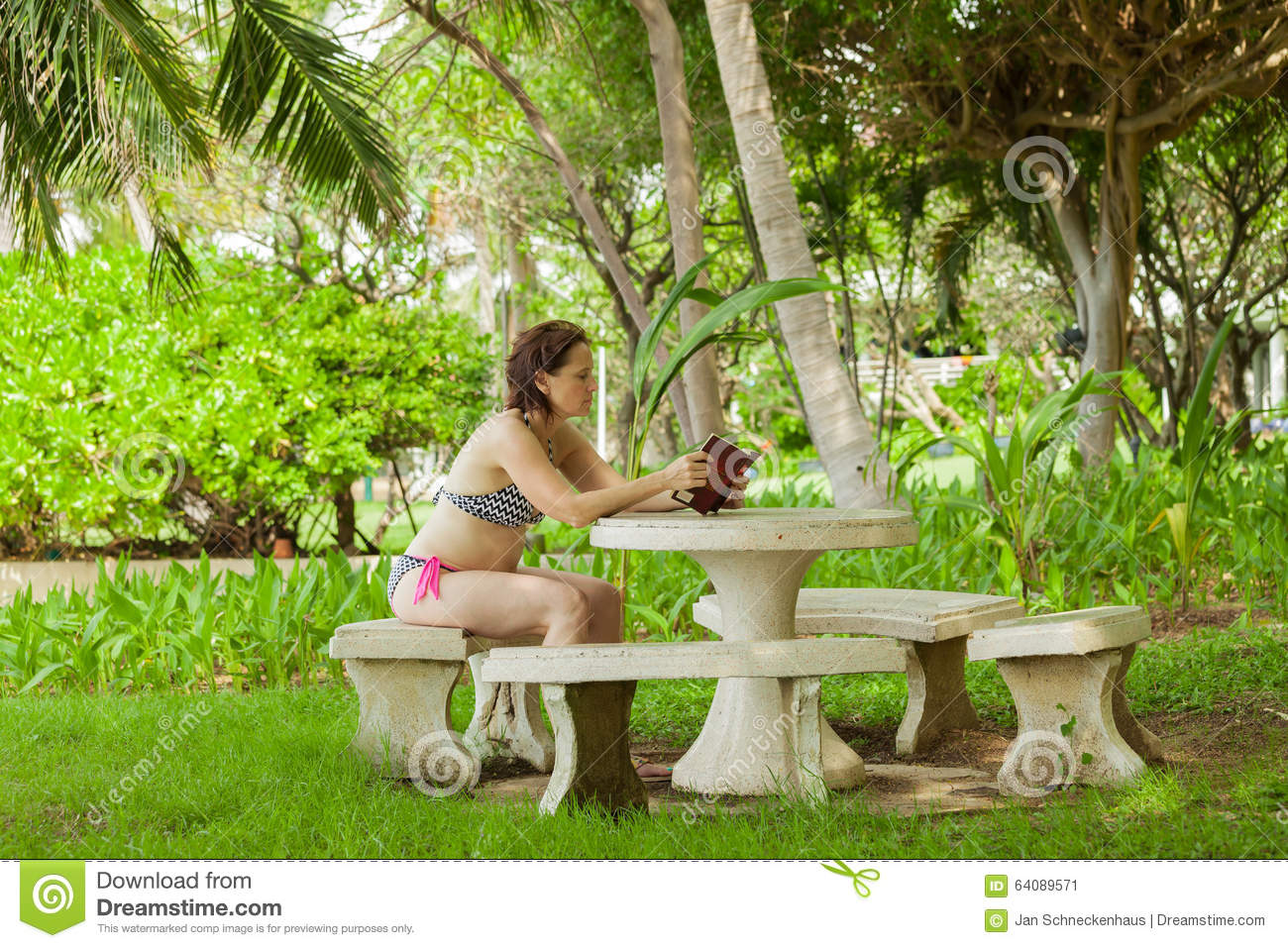 A Woman Reading A Book In The Garden Stock Photo Image