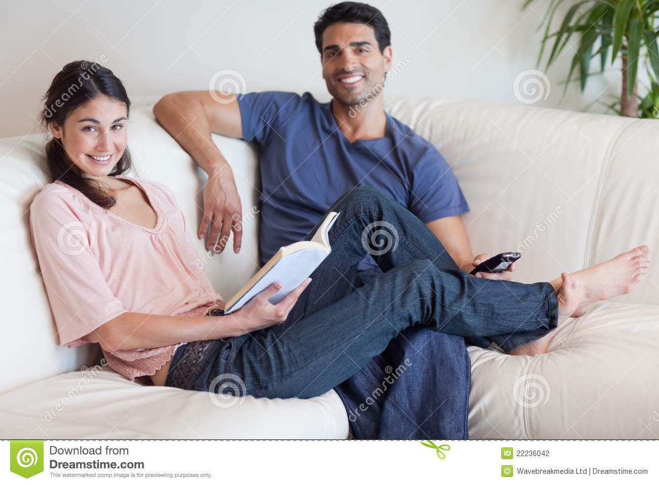 Woman Reading A Book While Her Husband Is Watching TV ...