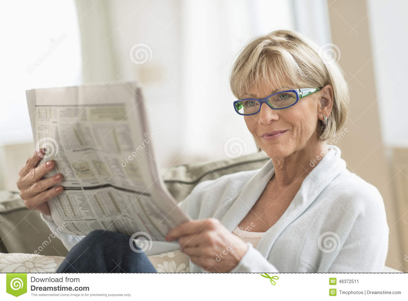 Woman Reading Newspaper While Relaxing On Sofa Stock Photo ...