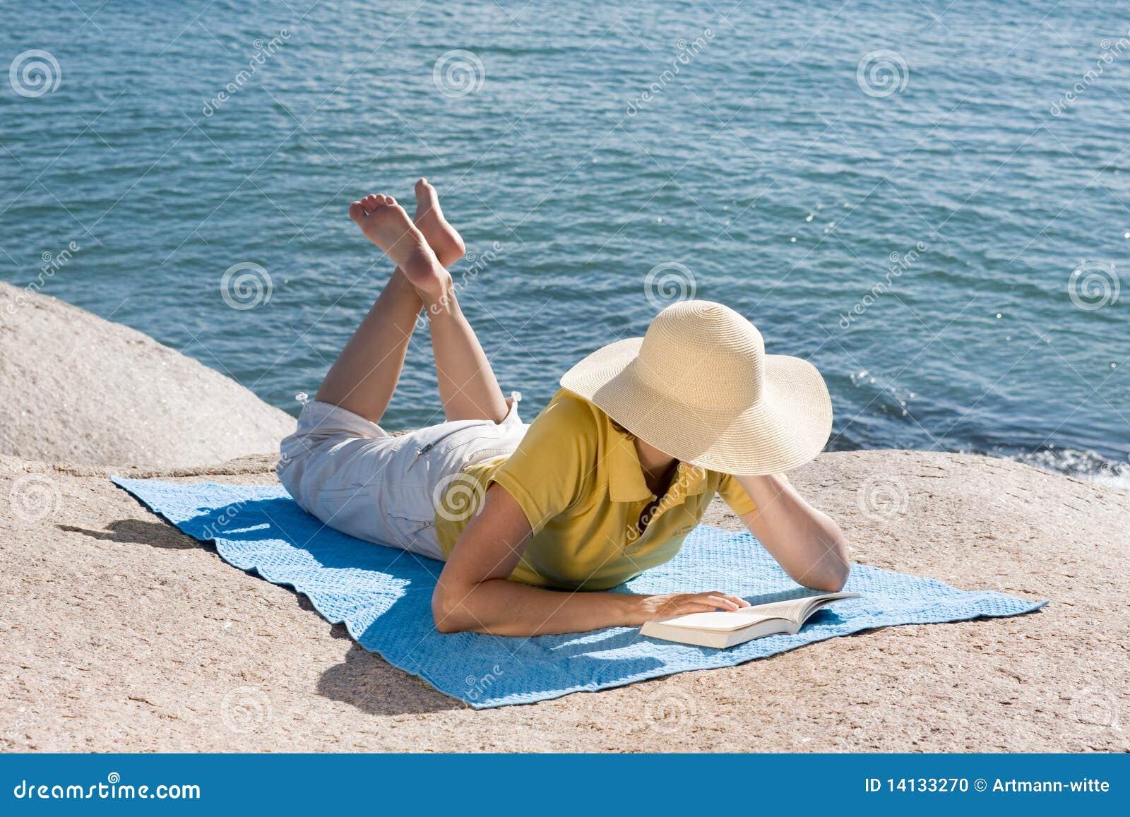 Woman reading at the sea