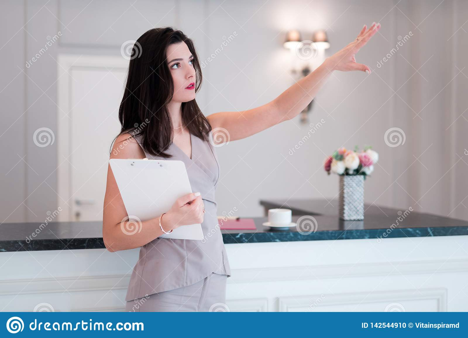 Woman realtor proposes to visit flat or apartment. Agent shows with hand something apartment.