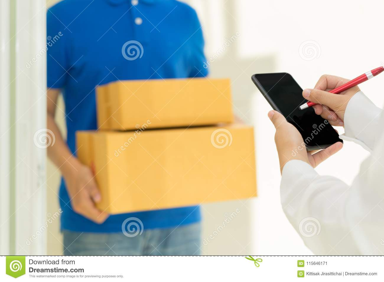 Woman receiving package and signing on digital mobile phone from