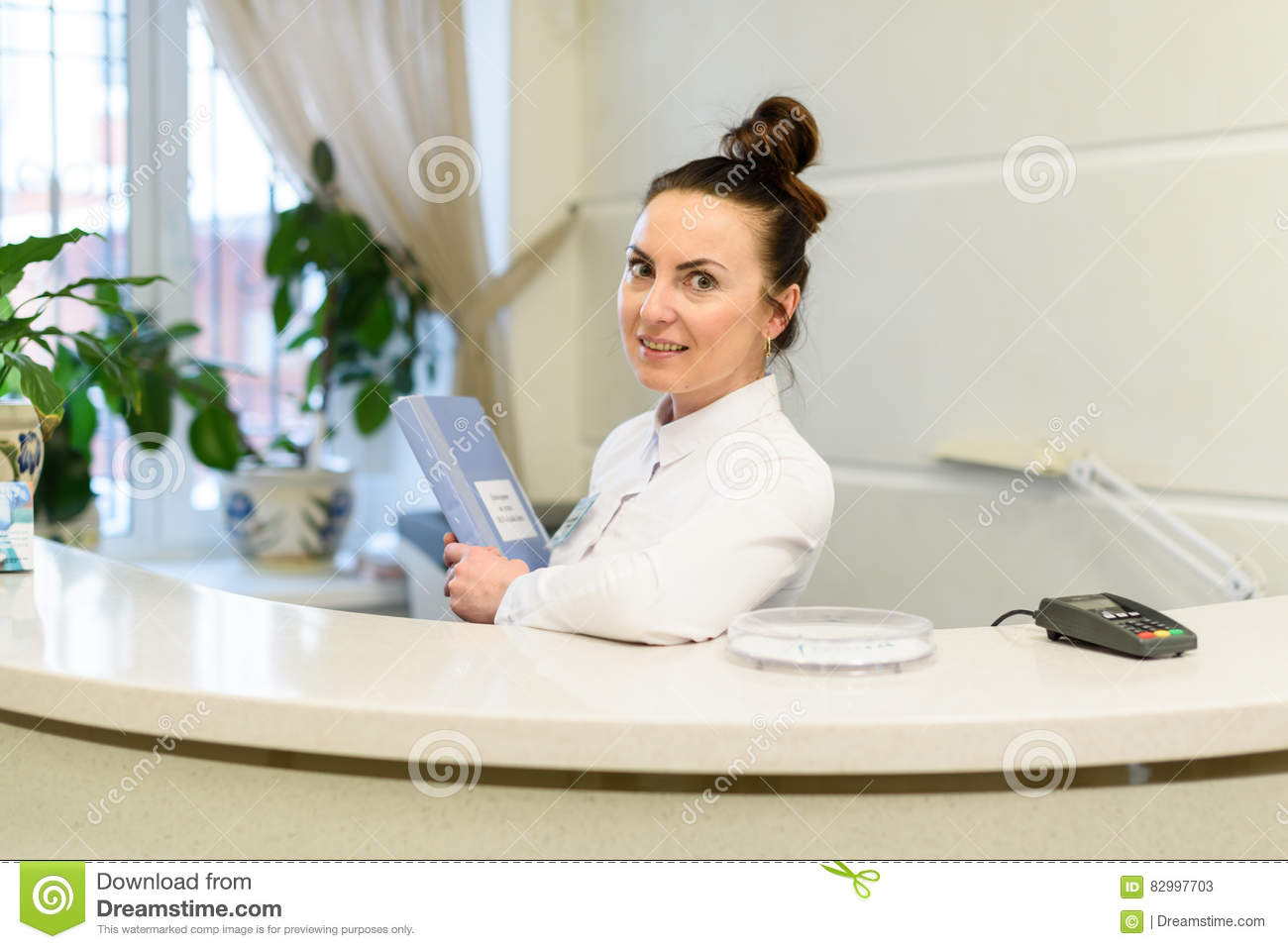 Woman receptionist in medical coat stands at reception desk