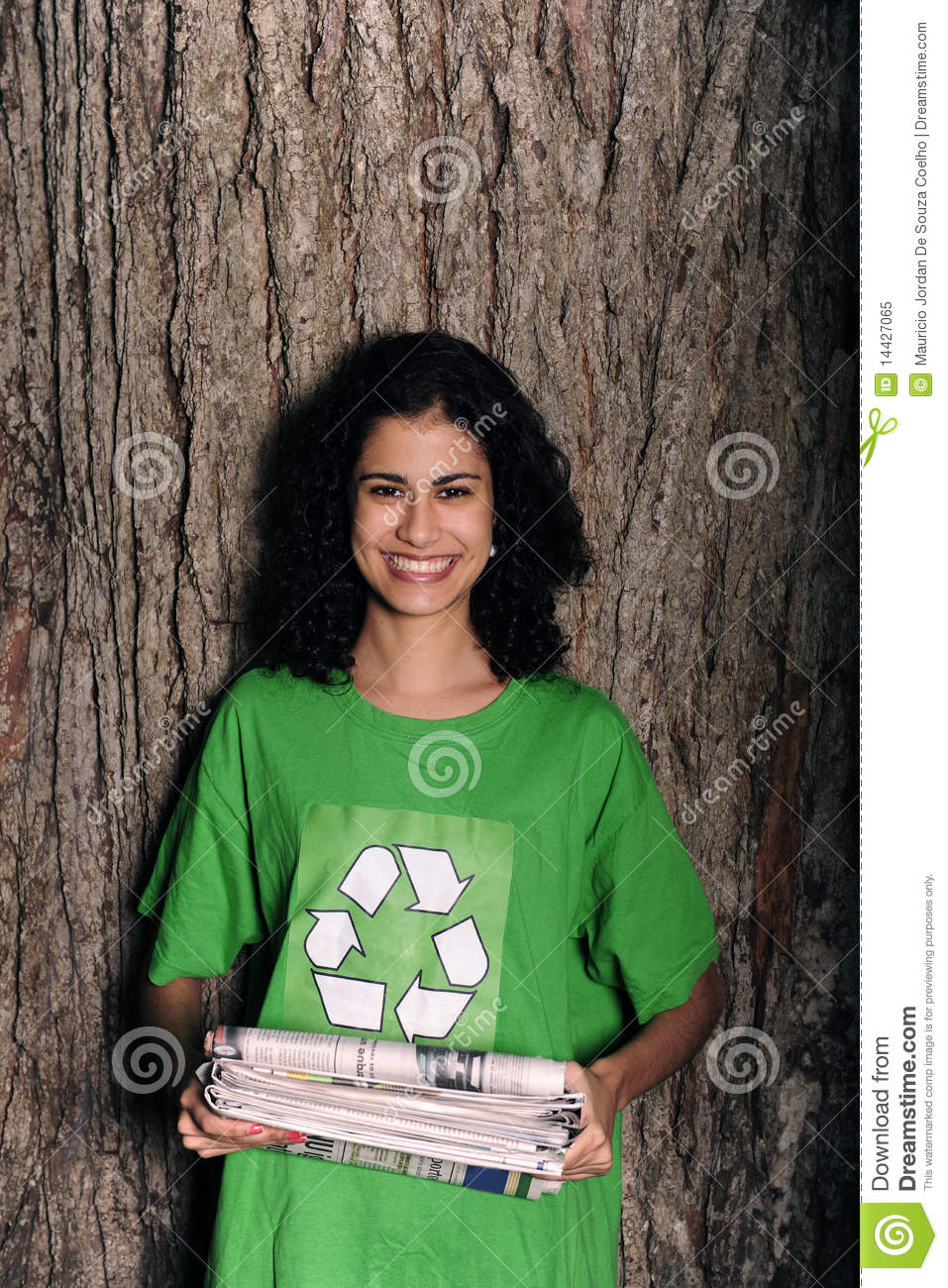 Woman with recycling sign holding newspapers