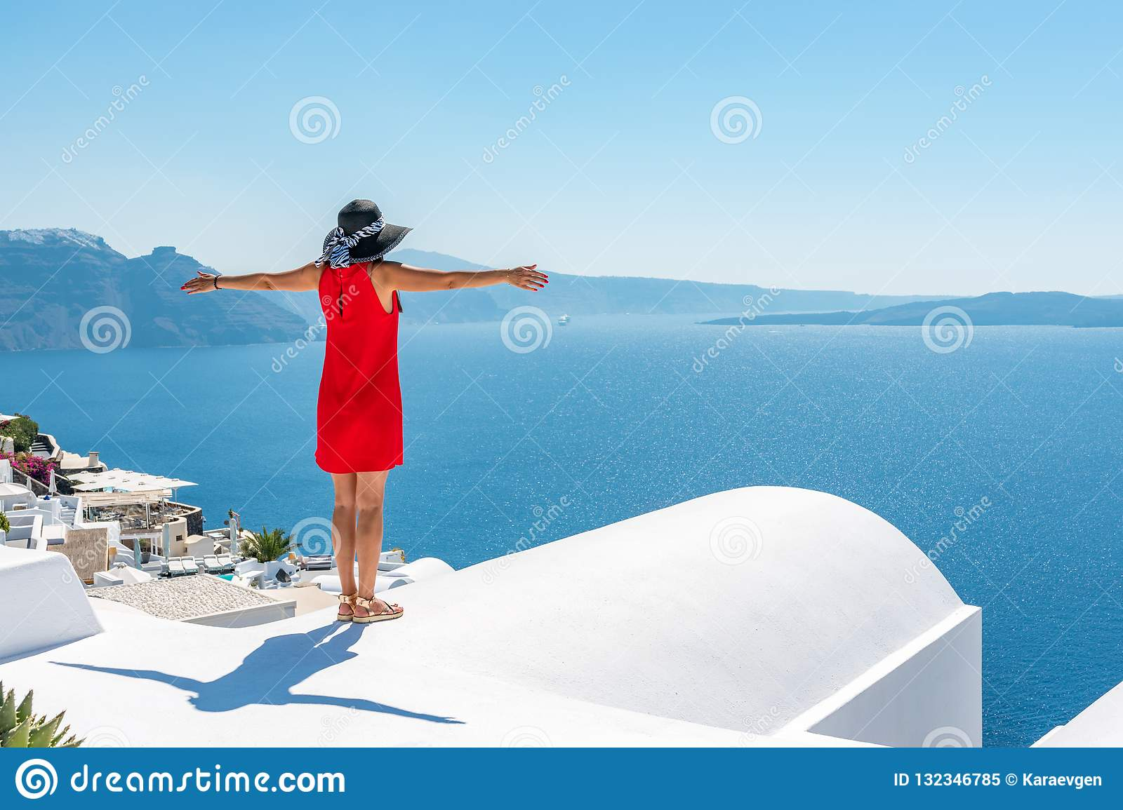 Woman in red dress on the roof enjoying view of Santorini island and Caldera in Aegean sea.