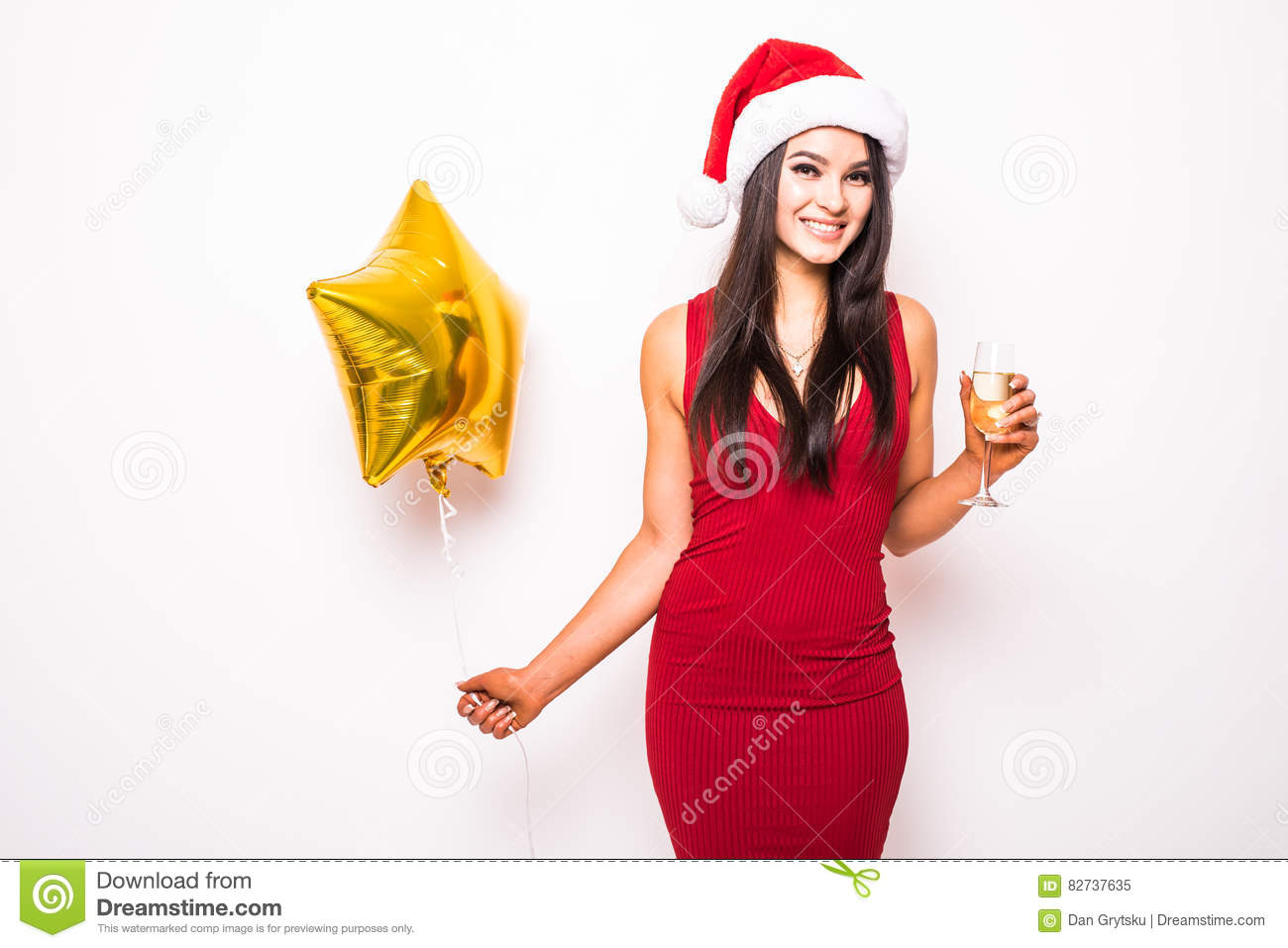 6956a86fb93f Pretty young woman in red dress and santa christmas hat with gold star  shaped balloon smiling and drinking champagne over white background