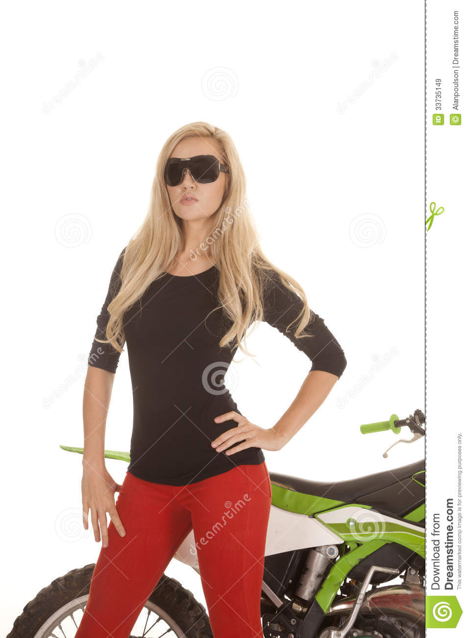 A woman in red pants and sun glasses in front of motorcycle