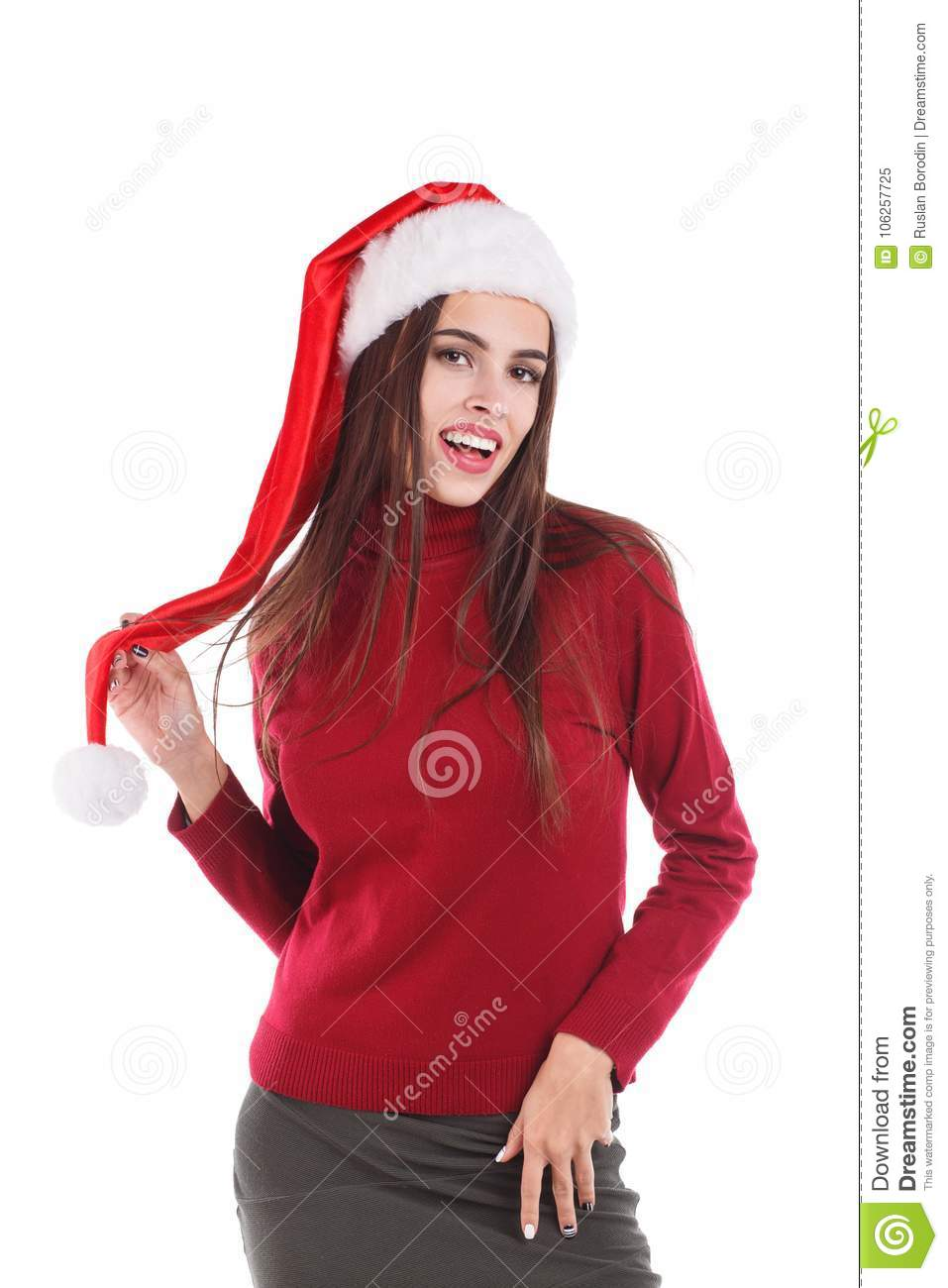 Woman In Red Sweater And Santas Hat Posing While Standing Holding Hand Over Fluffy Pompon Hat And Smiling Isolated