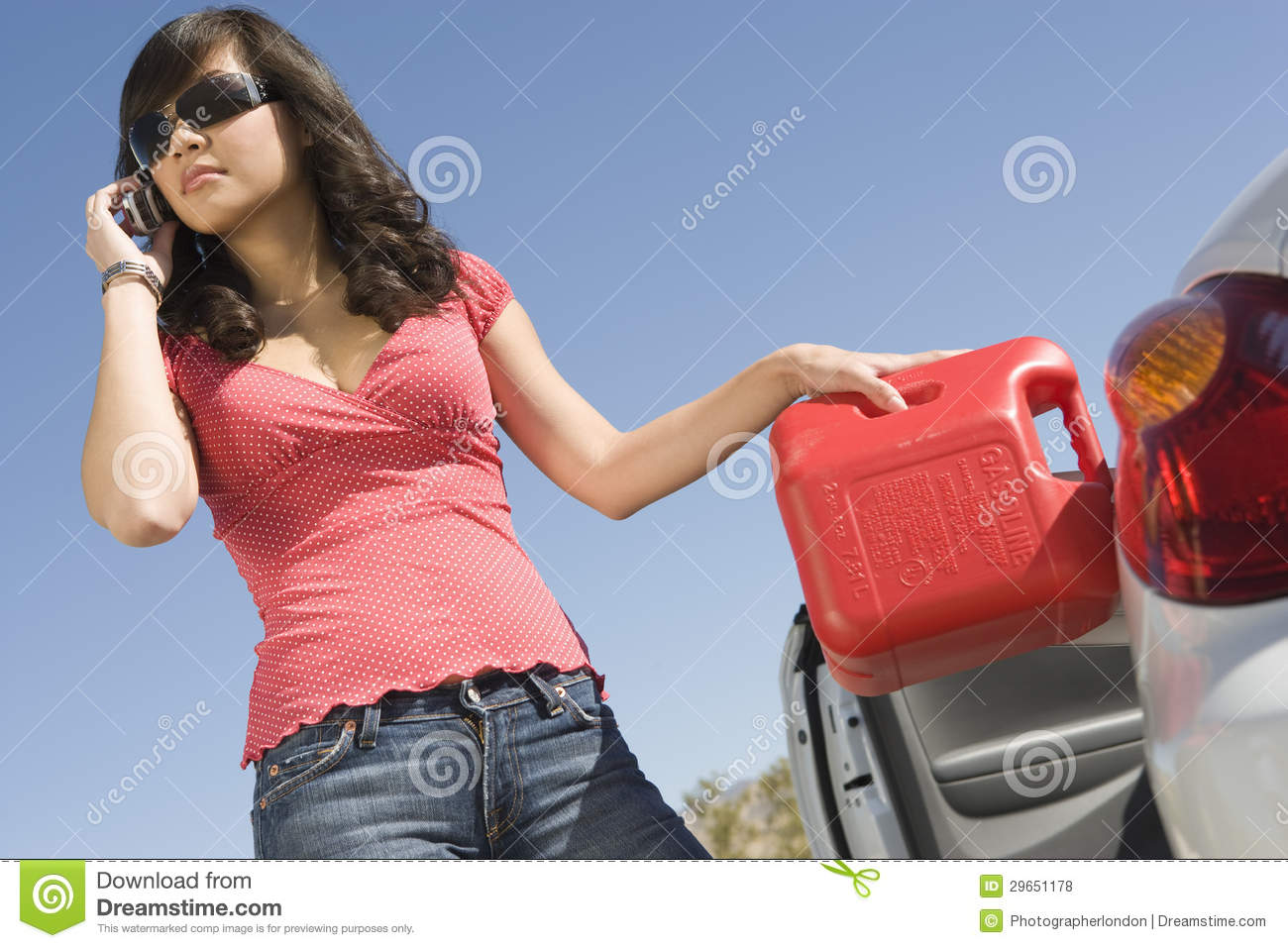 Woman Refueling Her Car While Talking On Cell Phone