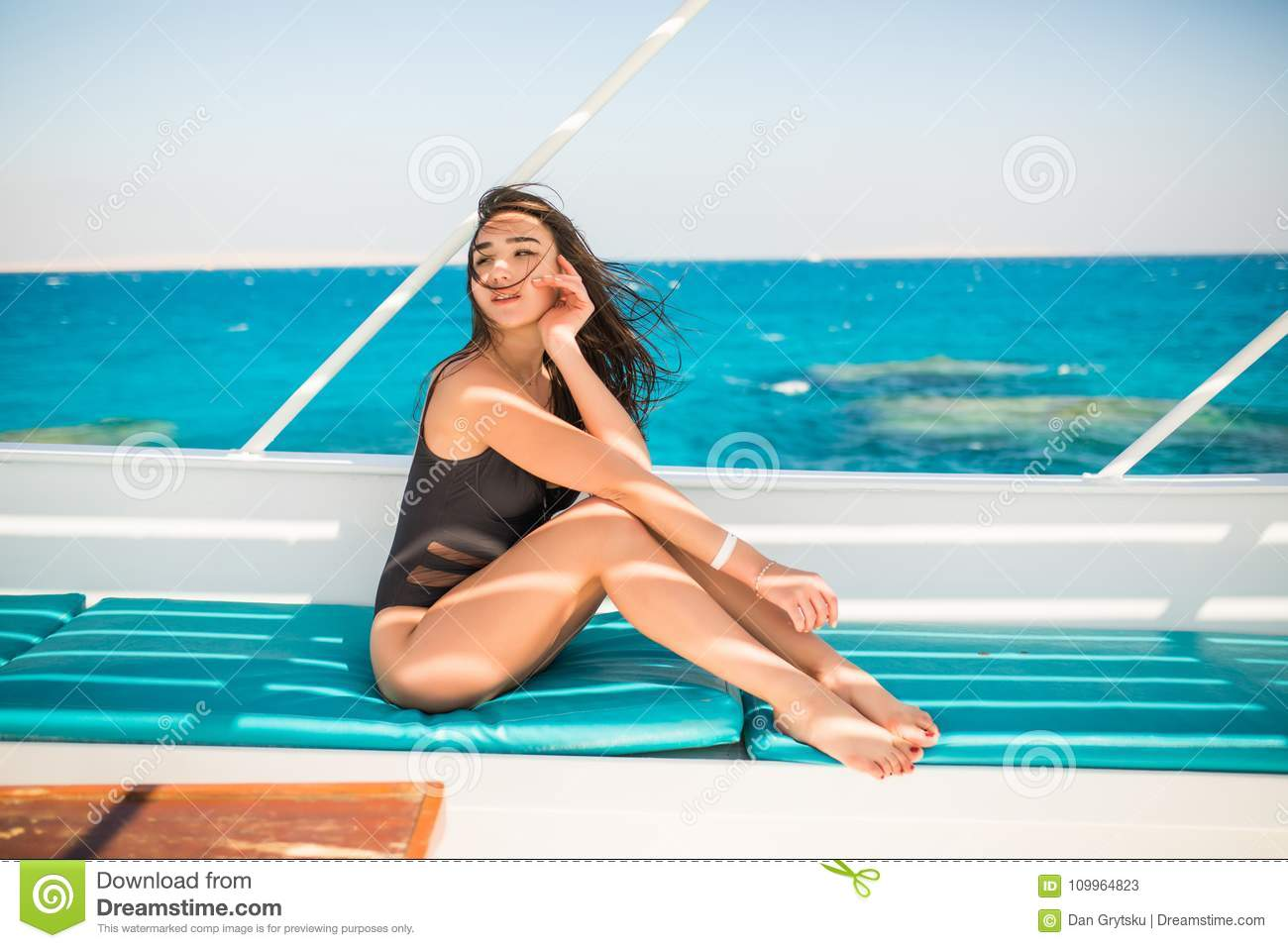Young Woman relaxing on board of sailing yacht in opean sea