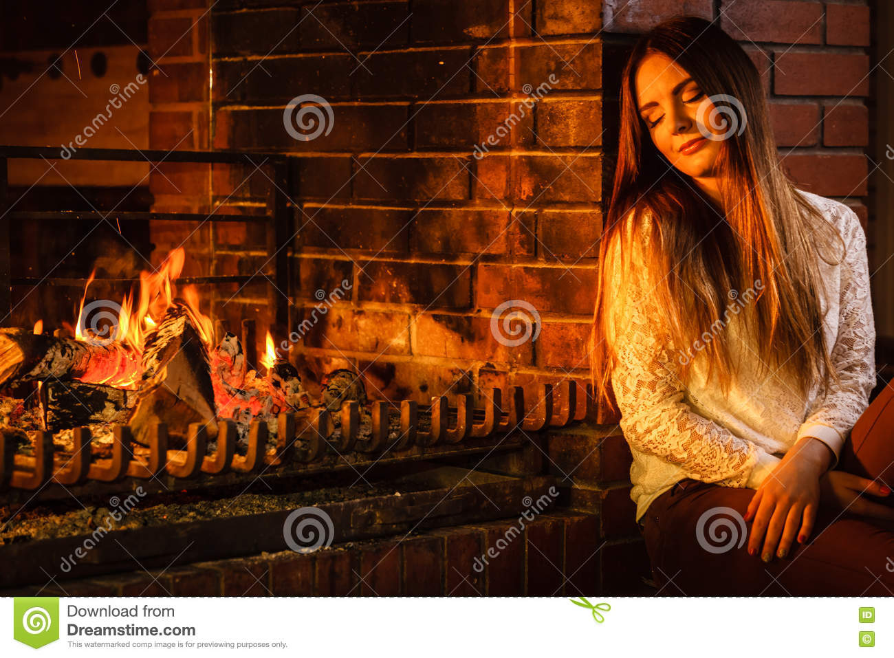 Woman Relaxing At Fireplace Winter Home Stock Photo