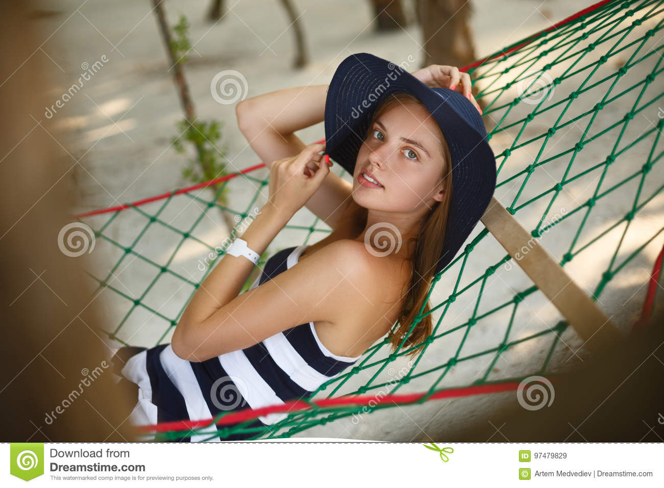 Woman relaxing in the hammock on tropical beach in the shadow, hot sunny day. Girl looks to camera with smile