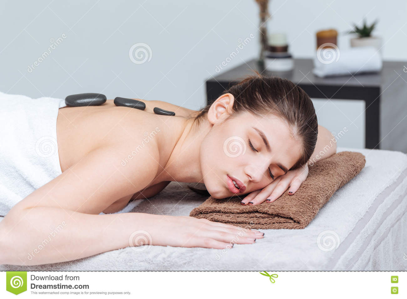 Sensual Young Woman Relaxing And Receiving Hot Stone Massage In Spa Salon