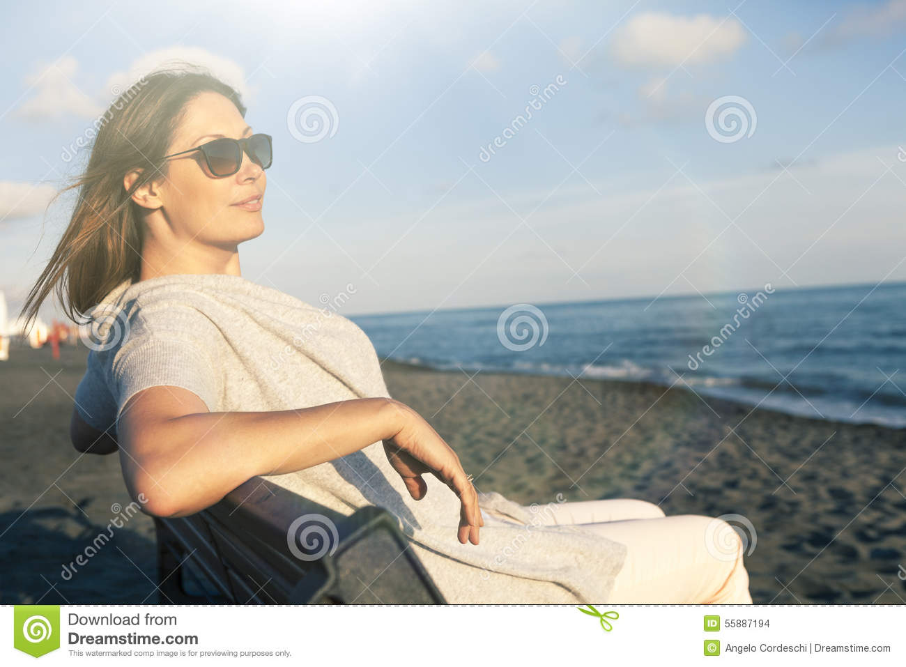 Woman relaxing at the sea dressed in peace sitting on the bench on the beach. Sunglasses