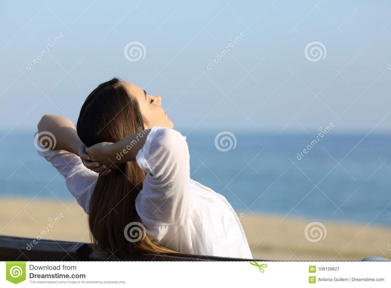 Woman relaxing on a bench on the beach