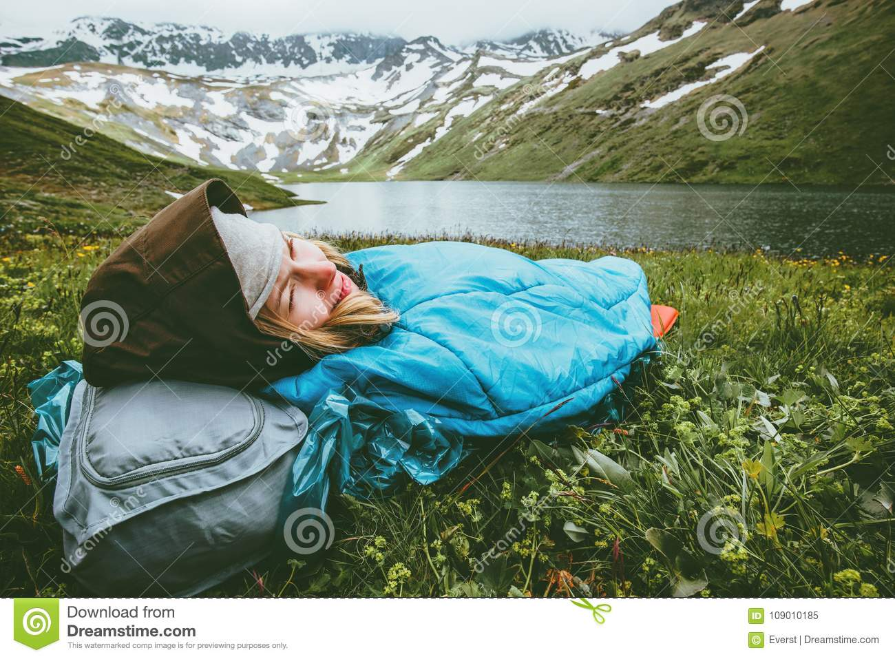 Woman relaxing in sleeping bag laying on grass enjoying lake and mountains
