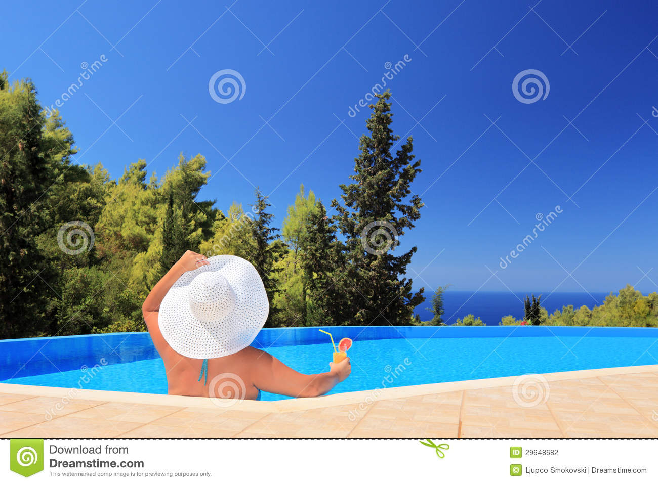 A woman relaxing in a swimming pool with cocktail