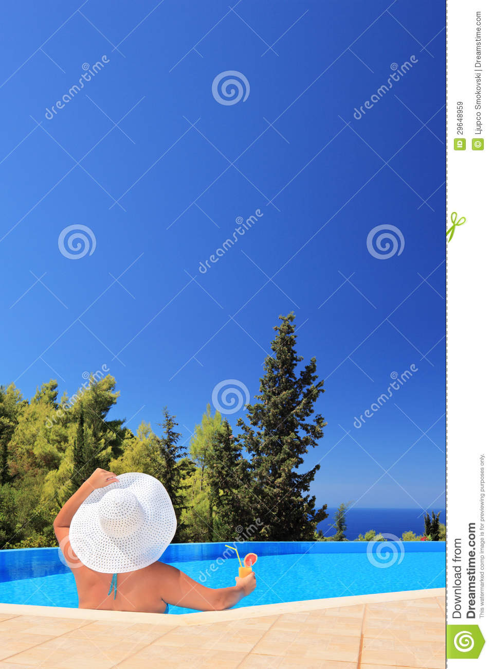 Woman relaxing in a swimming pool with cocktail