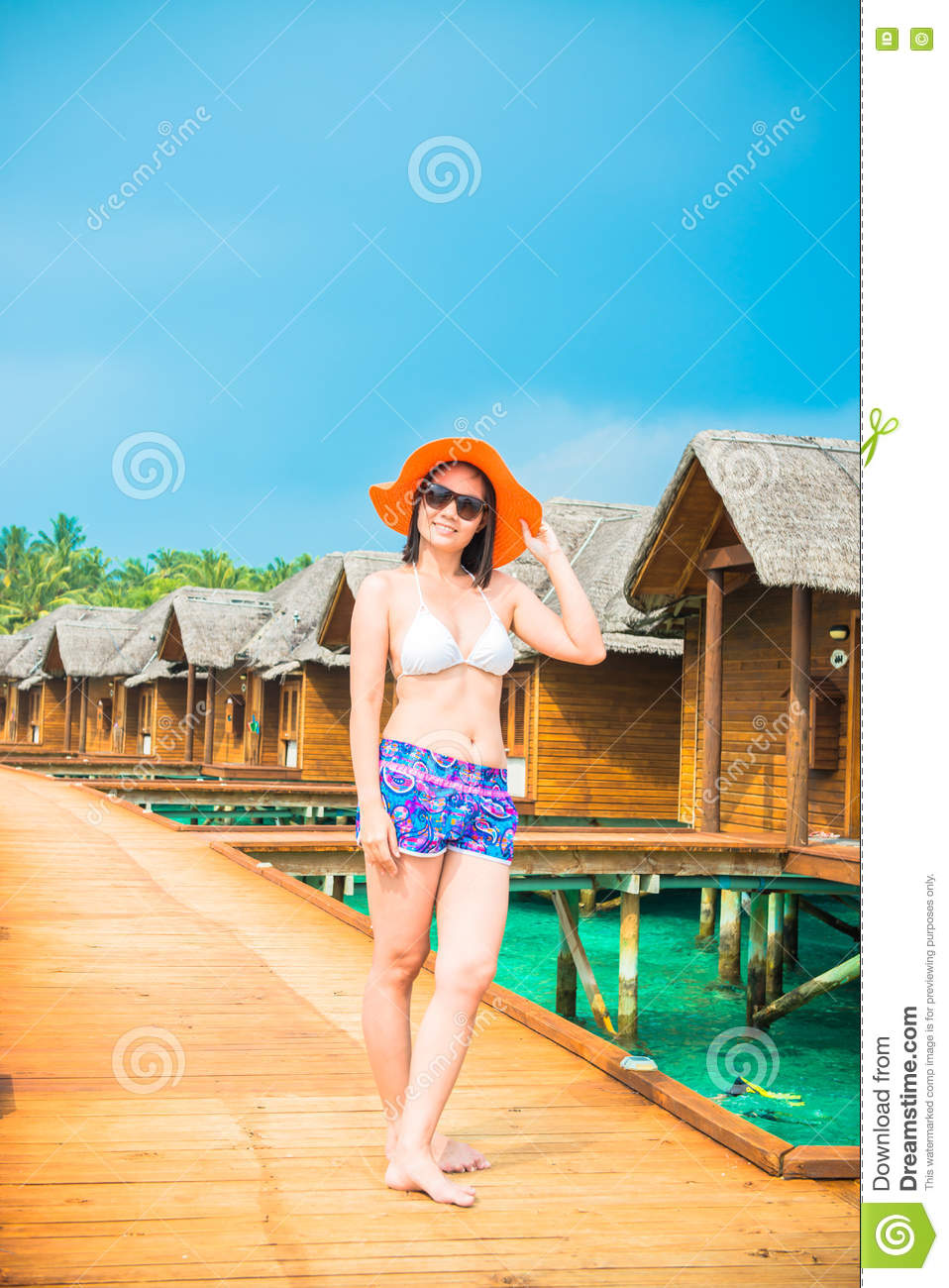 Woman is relaxing on the water bangalow of the tropical beach