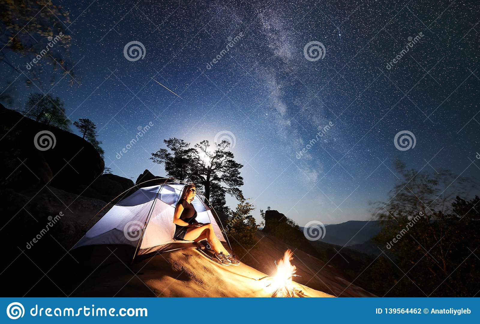 Woman resting beside camp, bonfire and tourist tent at night