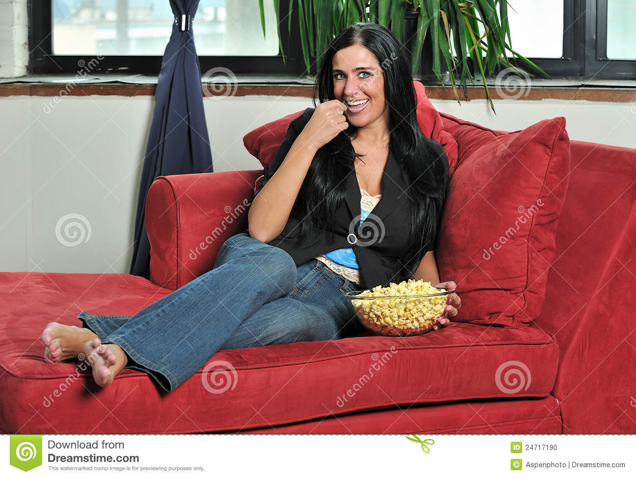 Woman resting barefoot on red chaise lounge chair eating popcorn