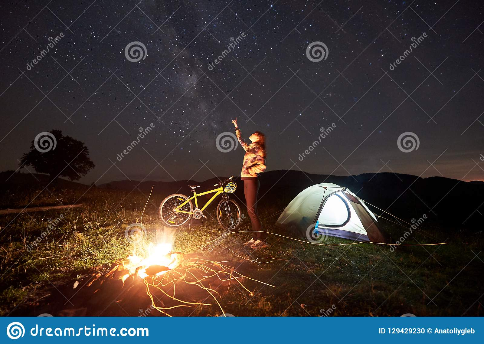 Woman resting at night camping near campfire, tourist tent, bicycle under evening sky full of stars