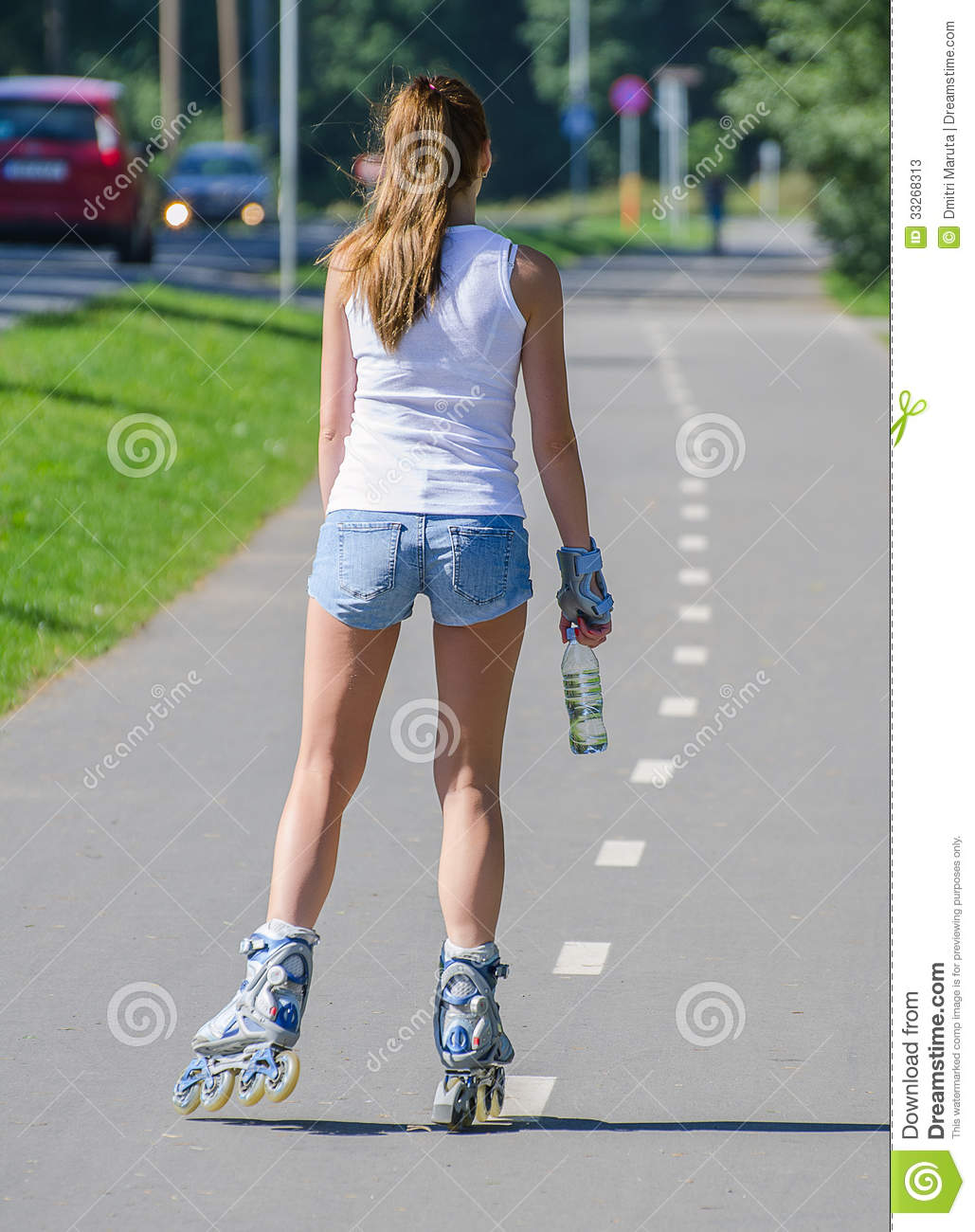 woman ride rollerblades in the park back view stock