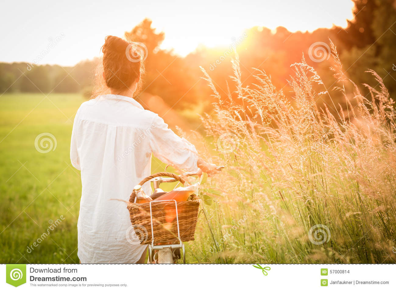 Woman riding bicycle with the basket of fresh food.